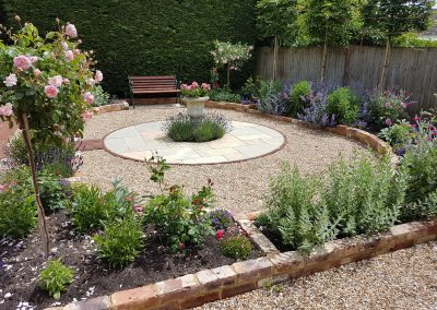 Roses, lavenders and low-maintenance shrubs around a central feature