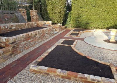 A mixture of bricks, gravel and natural stone before planting