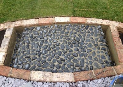 Black pebble and Victorian brick pond. Family garden Brighton