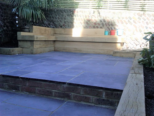 Black limestone stepped patio with oak benches