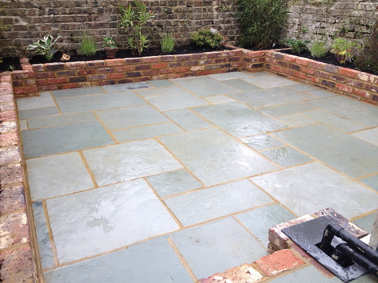 Blue limestone patio with reclaimed Victorian brick raised beds