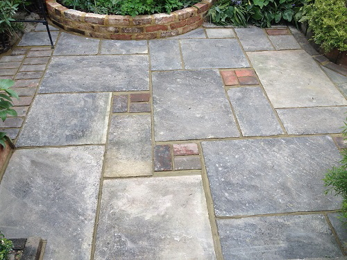Mixed stone patio with curved raised bed from Victorian bricks