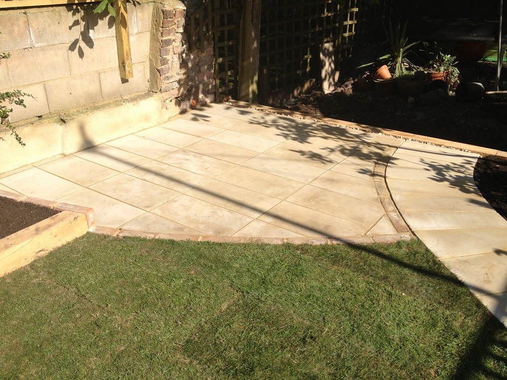 Turfed lawn leading to yellow limestone patio