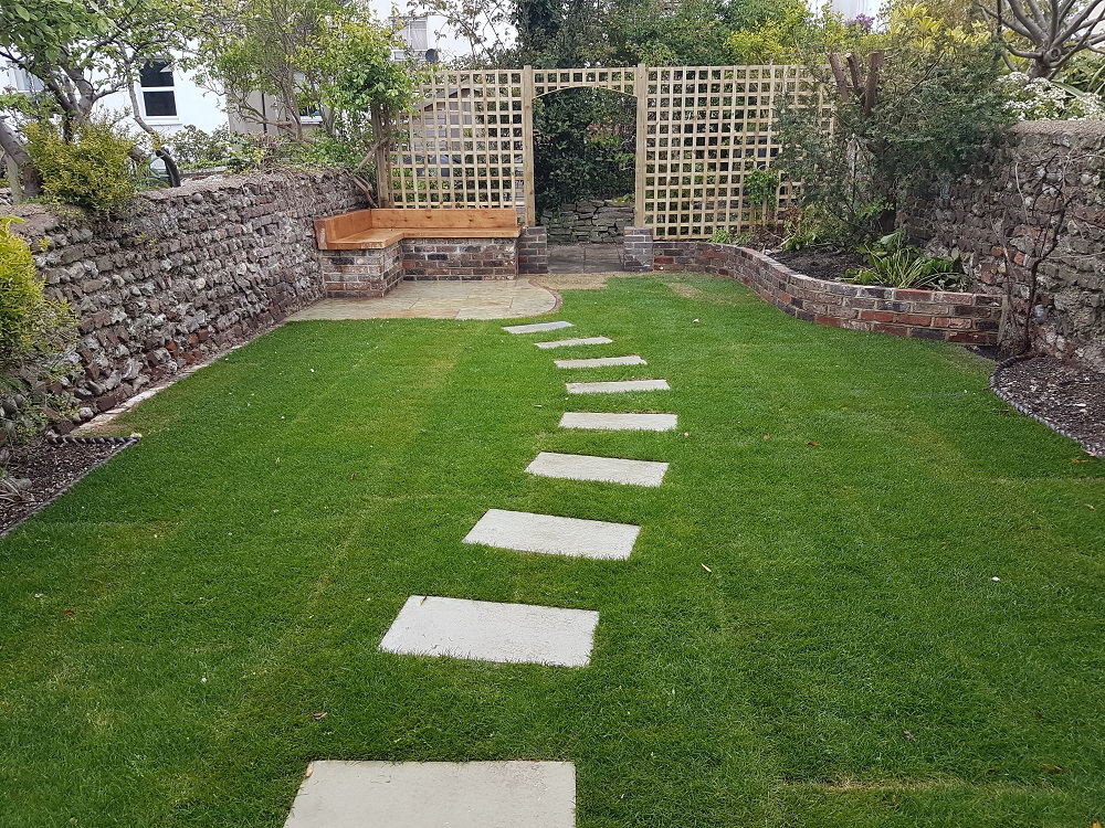 Turfed lawn leading to limestone patio and oak garden storage benches