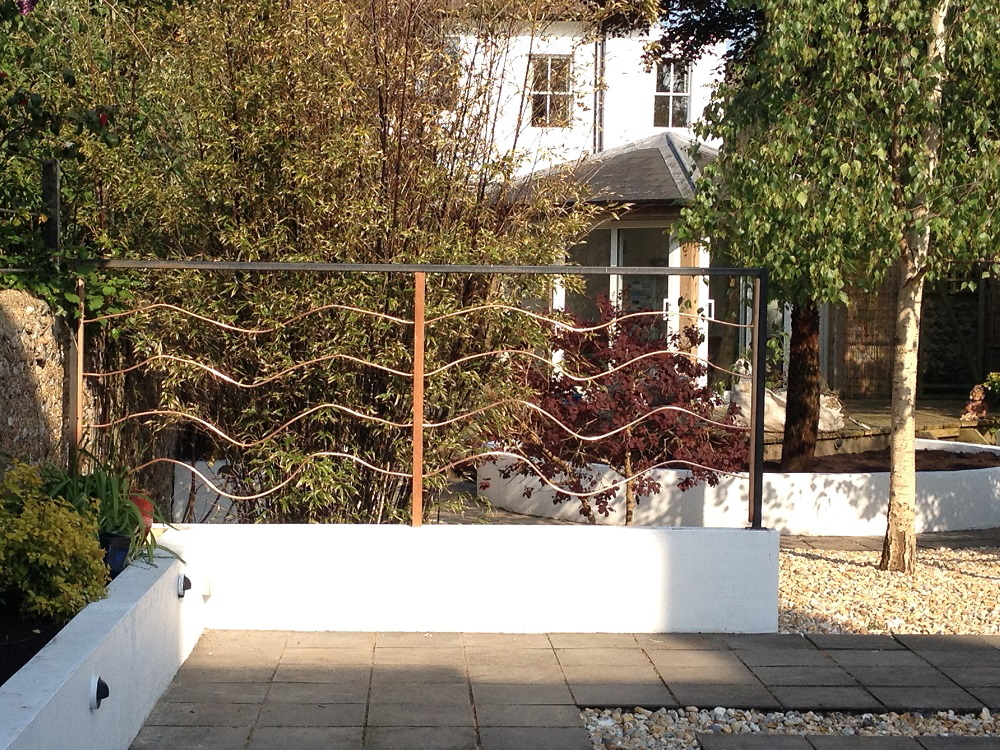 Bespoke iron screening on a smooth plastered low garden wall