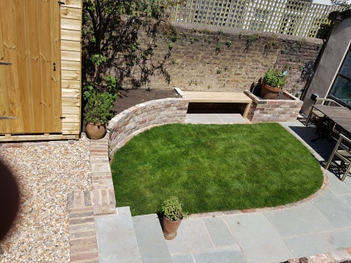 Levelled and turfed lawn, blue limestone patio and raised brick planters