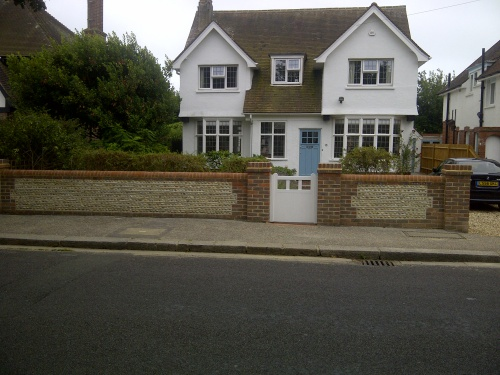 Brick and flint wall with garden gate