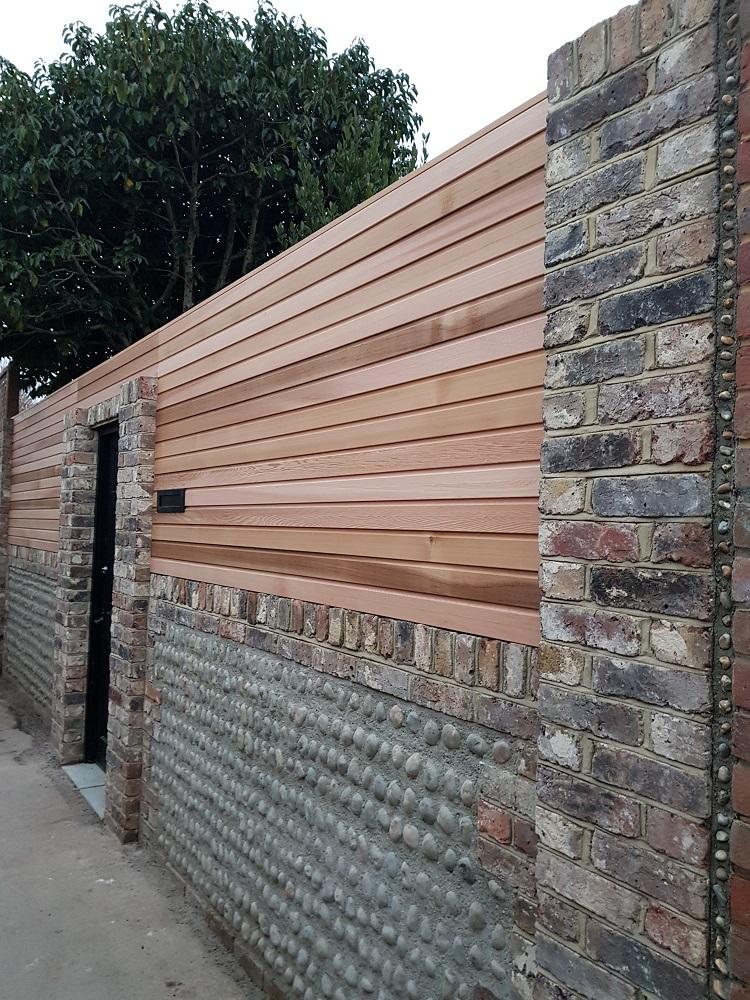 Cedar screen above a traditionally built flint wall