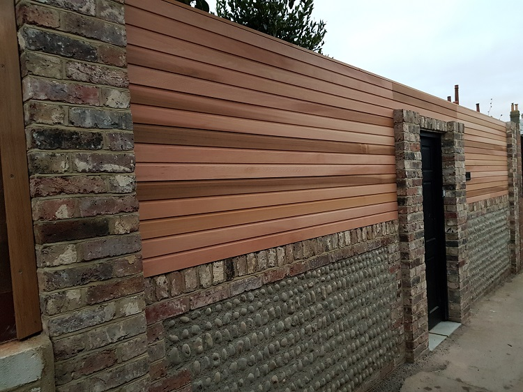 Cedar screen above a traditionally built flint wall