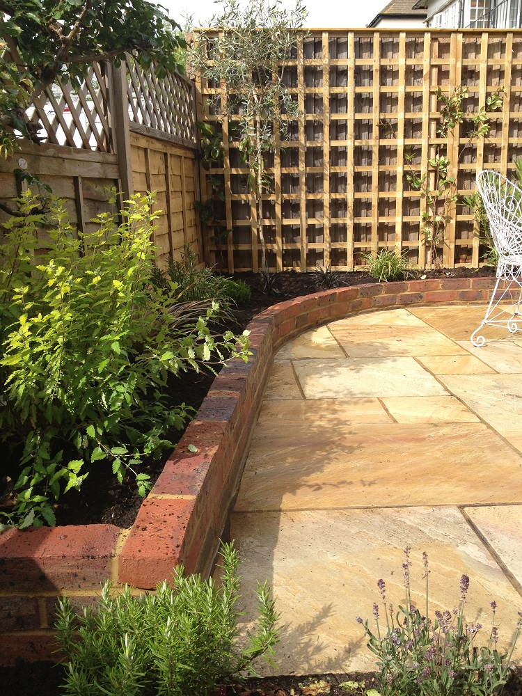 Yellow limestone patio, oak sleeper beds and Victorian brick beds